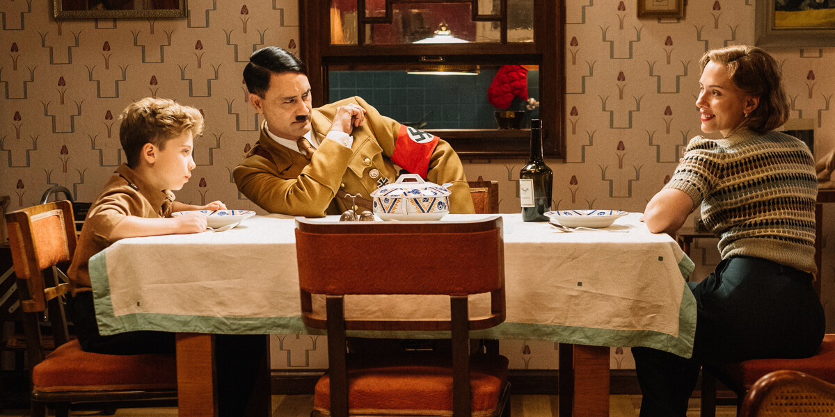 A still from the film, Jojo Rabbit. (Left to right): Jojo (Roman Griffin Davis) has dinner with his imaginary friend Adolf (Writer/Director Taika Waititi), and his mother, Rosie (Scarlet Johansson). Photo by Kimberley French. © 2018 Twentieth Century Fox Film Corporation All Rights Reserved