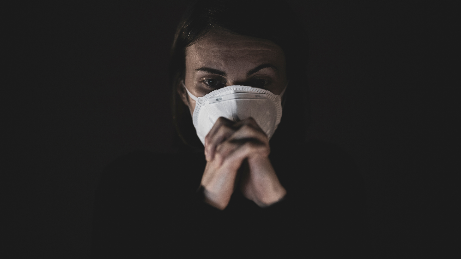 woman in mask sits in the dark with a worried look on her face. mental health