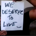 """Screenshot of restaurant worker, Md Masud Rana, holding a placard reading """"WE DESERVE TO LIVE."""", COVID-19, benefits, employment"""