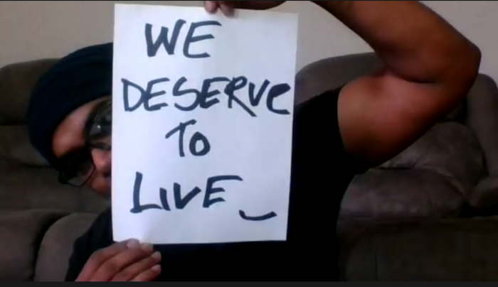 "Screenshot of restaurant worker, Md Masud Rana, holding a placard reading ""WE DESERVE TO LIVE."", COVID-19, benefits, employment"