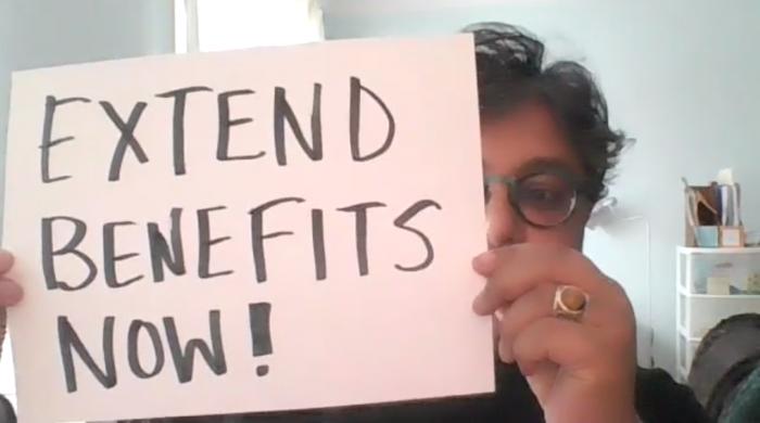 "WAC executive director, Deena Ladd, holds a placard reading ""EXTEND BENEFITS NOW."", benefits, employment"