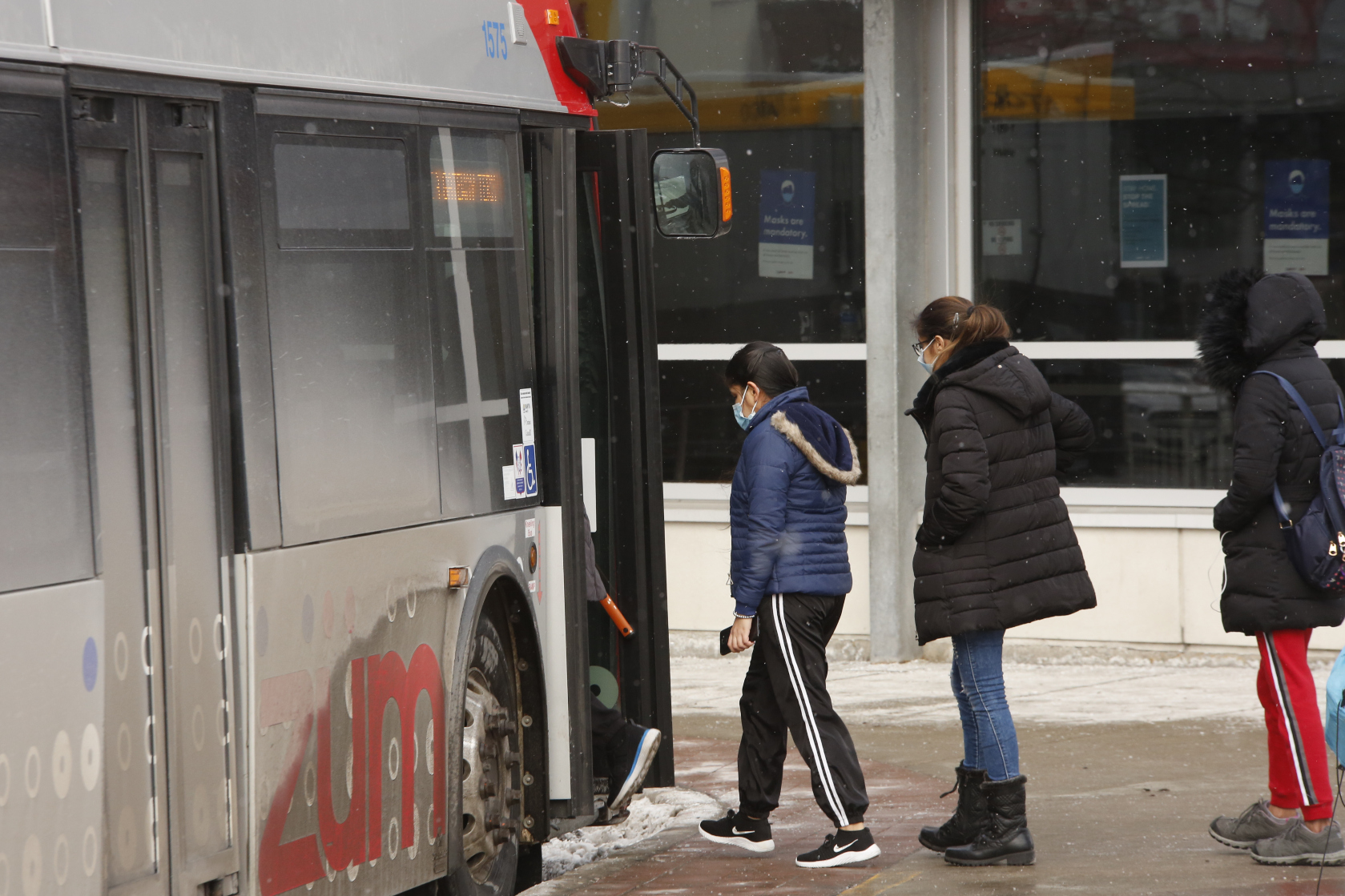 Photo of people lining up to get on a bus operated by Brampton Transit.