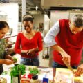 Three people at a table preparing food as part of a program to reduce food insecurity among who are living in transitional housing or experiencing homelessness.