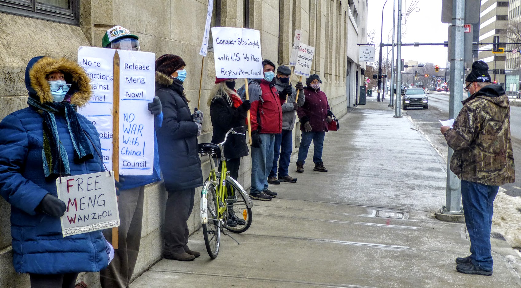 """Seven people in winter clothing and face masks line the street in Regina, holding placards that read: """"Free Meng Wanzhou,"""" """"No sanctions against China,"""" """"No war with China."""""""