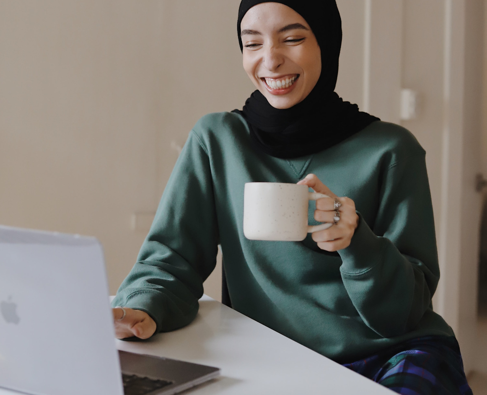 Photo of a woman in front of a laptop, wearing a sweatshirt and pajama pants, holding a mug.