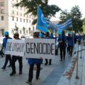 """Protesters in Washington, D.C., carry a placard saying """"The Uyghur genocide."""" Uyghurs are targetted by China's transnational repression campaign."""