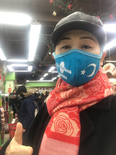 Photo of Sheng Xue wearing a face mask with a message supporting Uyghurs, who are targetted by China's transnational repression campaign.