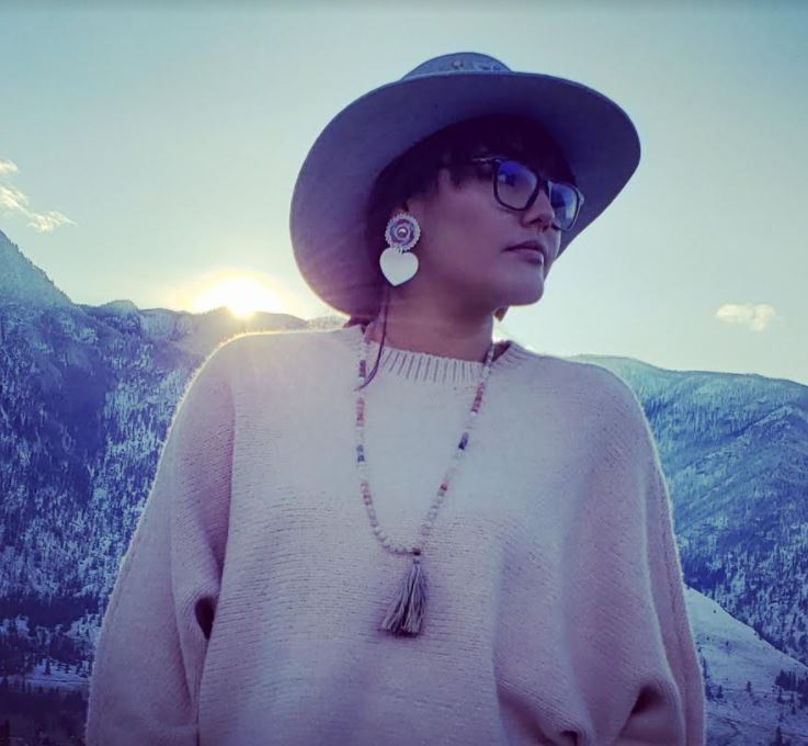 Lambert wearing the earrings and hat she beaded for her sister's photoshoot of modern Indigenous art.