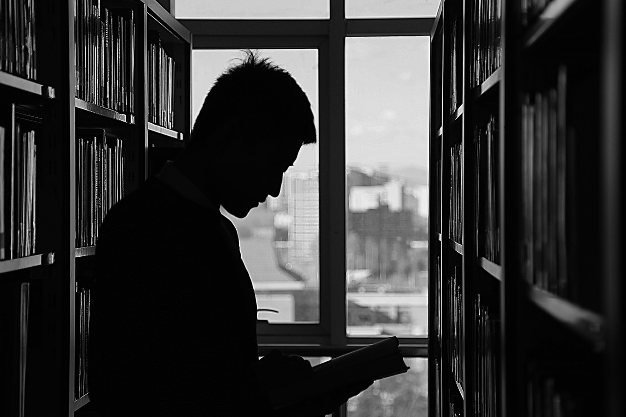 Dark silhouette of a student in a library.