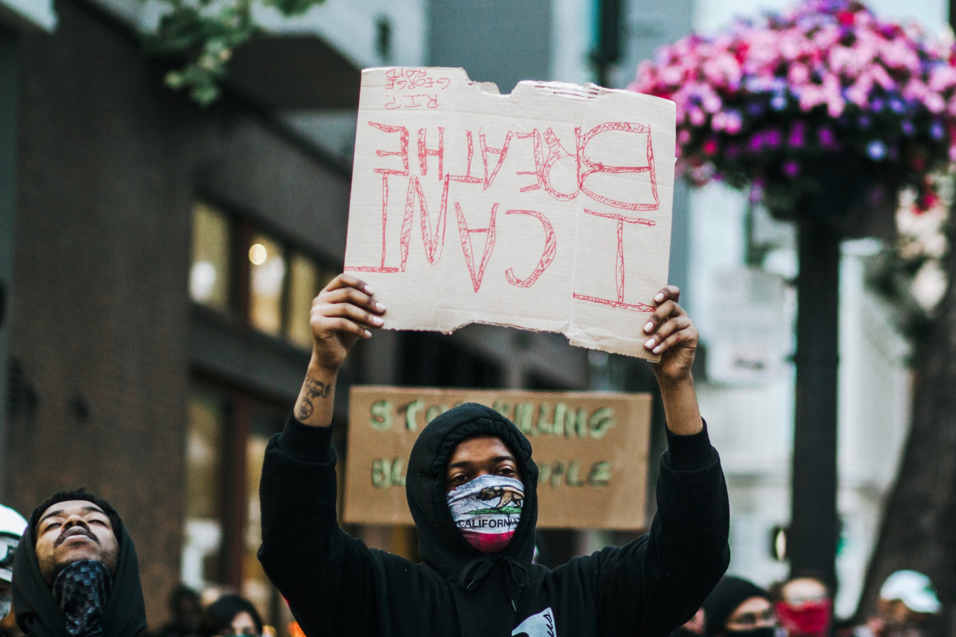 """Many protests took place before the Derek Chauvin trial. Picture here is a protestor holding an upside down sign that reads """"I can't breathe."""""""