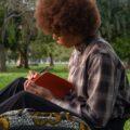 Une jeune fille écrit dans un cahier dans un parc