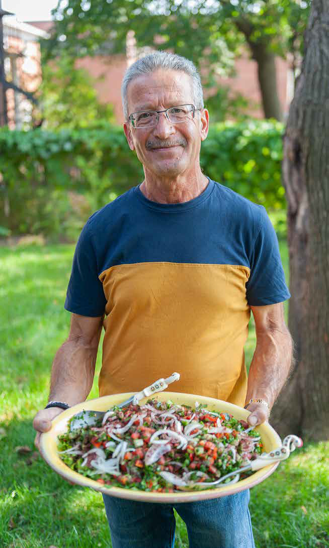 Cook holding a plate of his dish