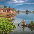 """A woman rowing a boat known as """"Shikara"""" in Srinagar, Kashmir, where the novel """"Life in the Clock Tower Valley"""" is set."""