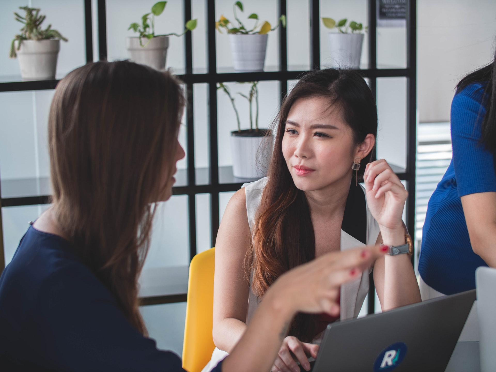 Two women talking in an office space. Microaggressions often happen in everyday life.